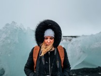 Blond cute female in warm hooded outerwear looking at camera against gray sky in countryside on winter day in Iceland, M