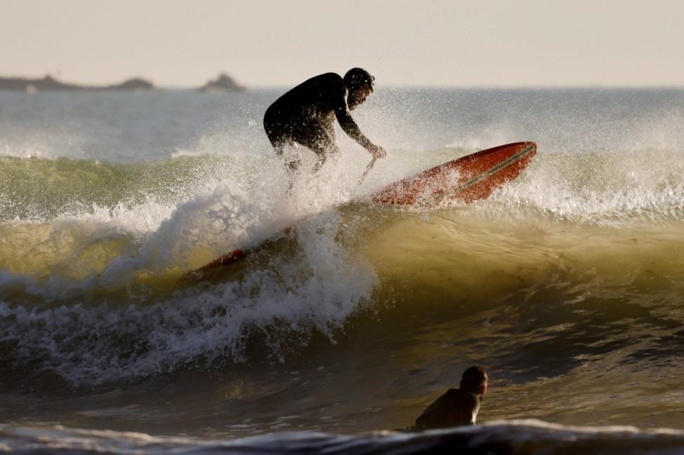 A man on a paddle board surfs at la Guerite-Tata Beach in Plouharnel, Quiberon Peninsula, Brittany, France,
