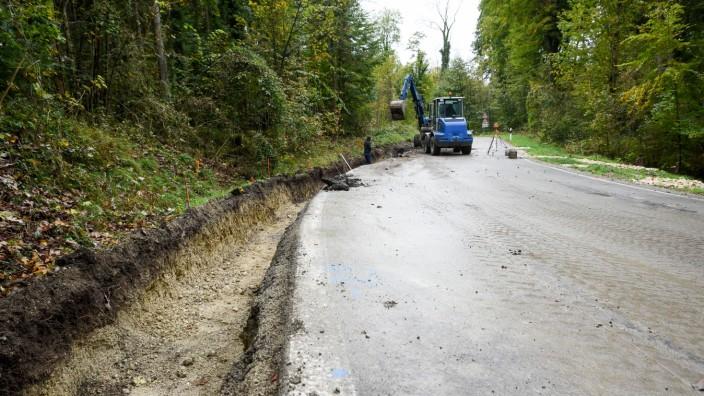 Klimawandel: Stabilisieren und Entwässern: Ein Bagger gräbt die Hangseite auf, wo die Staatsstraße künftig verbreitert werden soll, damit mehr Last am Berg bleibt.