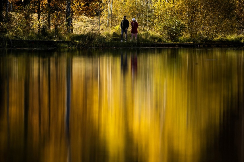 People walk on the embankment of a pond during sunny autumn weather in Moscow