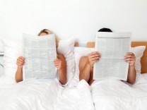 Ein junges Paar im Bett liest die Zeitung. Information und Nachrichten, McPBBO *** Young couple in bed reading the newsp