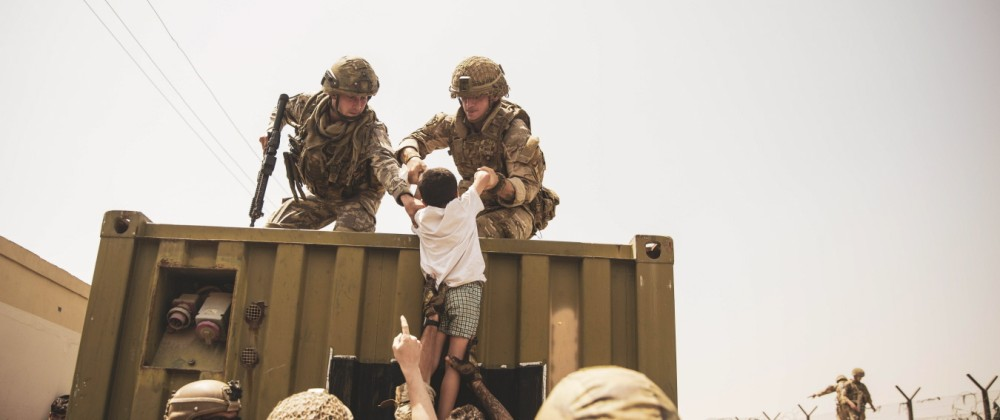 United Kingdom coalition forces, Turkish coalition forces, and United States Marines assist a child during an evacuation