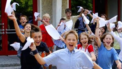 Kritik an guten Noten: Zeugnis-Jubel: Kinder freuen sich über gute Noten. Doch Lehrer können Probleme bekommen, wenn ihre Schüler zu gute Noten schreiben.