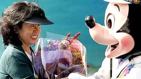 Reise-Knigge für Japan: Mickey-san gratuliert Hironaka-san, der 400-Millionsten-Besucherin von Disneyland in Tokio.