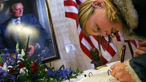 Eine junge Amerikanerin trägt sich in ein Kondolenzbuch ein
