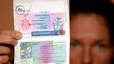 Eine Osteuropäerin zeigt ihren Pass mit Schengen-Visum, dpa