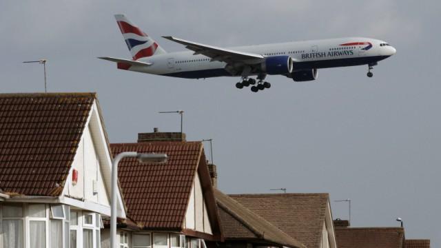 A British Airways airplane lands over homes near Heathrow Airport in London