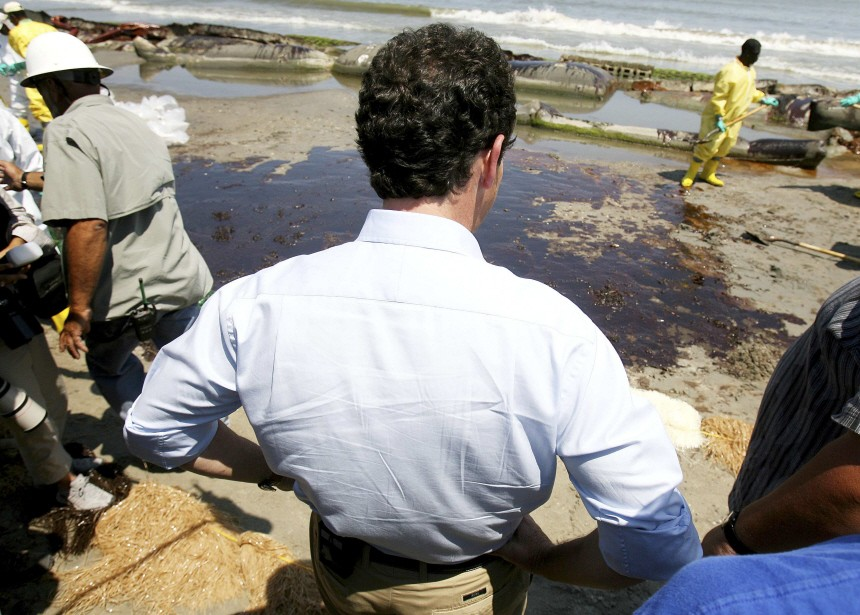 BP CEO Tony Hayward looks on as crew members clean up the beach in Port Fourchon, Louisiana