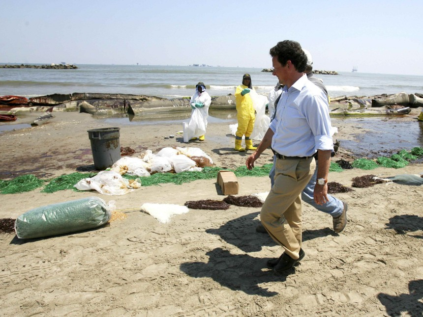 BP Chief Executive Officer Tony Hayward looks on as crew members clean up the beach in Port Fourchon