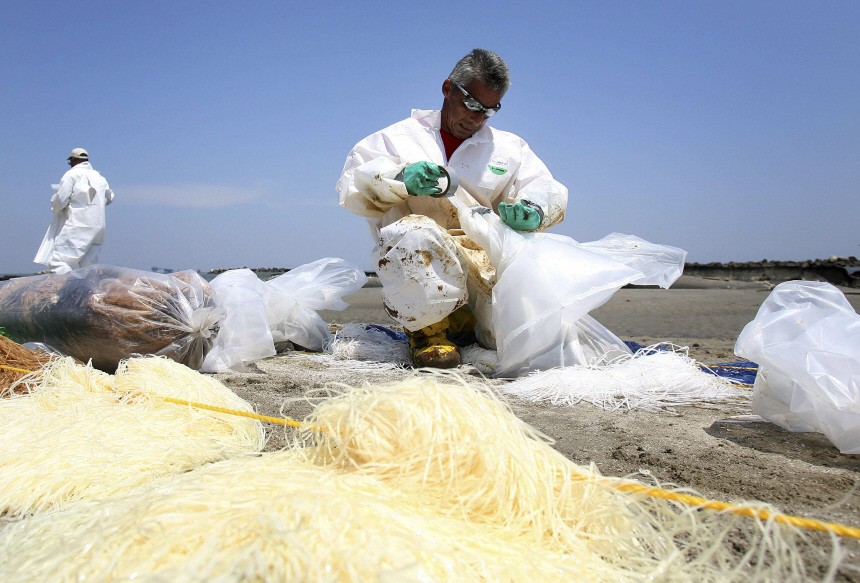 A crew member bags up oil stained snare boom along the beach in Port Fourchon