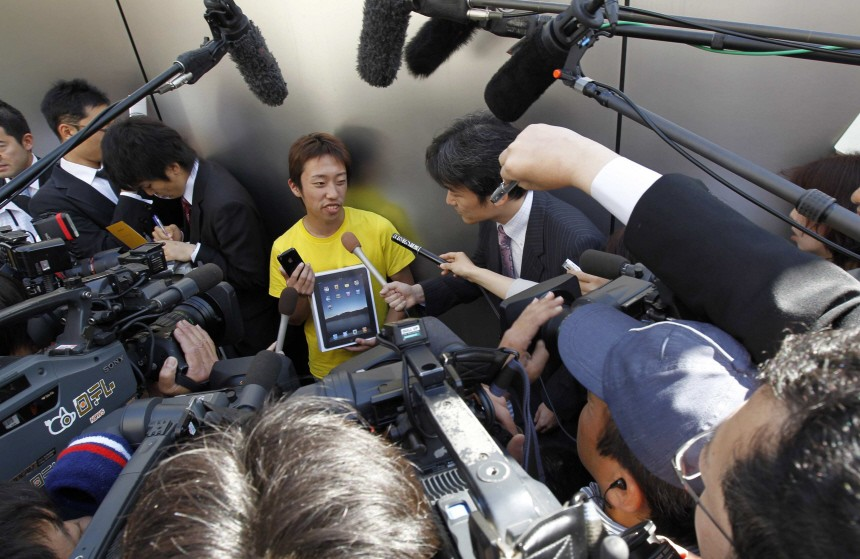 Takechiyo Yamanaka is surrounded by reporters after he bought an iPad at an Apple store in Tokyo