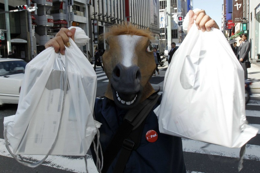 A man wearing a horse mask poses with his iPads after he bought them at an Apple store in Tokyo