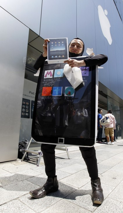 A man wearing a costume representing an iPad poses with his iPad after purchasing it at an Apple store in Tokyo