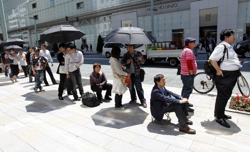 People stand in a line to purchase Apple's iPad at an Apple store in Tokyo