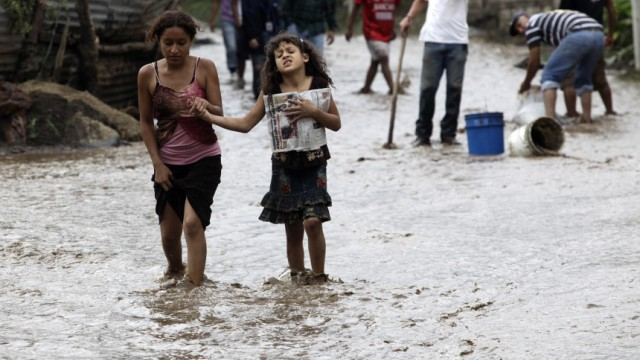 Two sisters walk down a street flooded by rains from Agatha in Amatitilan