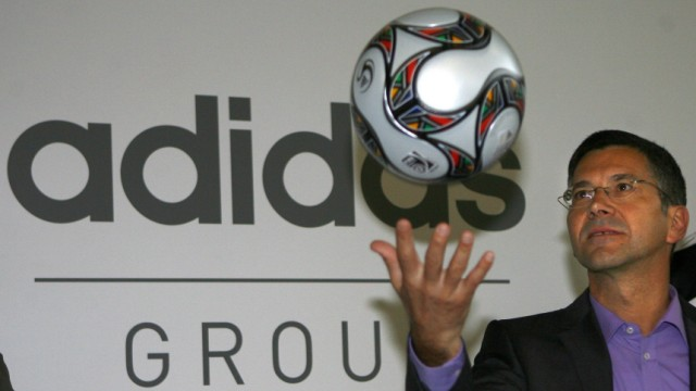 CEO of German sporting goods maker Adidas Hainer throws a soccer ball before the company's annual news conference in Herzogenaurach