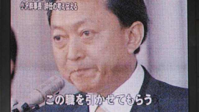 Pedestrians watch a news program about Japan's Prime Minister Yukio Hatoyama on a giant screen display in Osaka