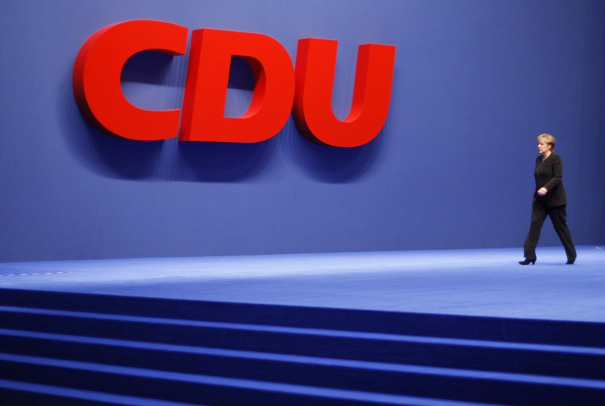 German Chancellor Merkel walks past a logo of the conservative CDU at the party congress in Hanover