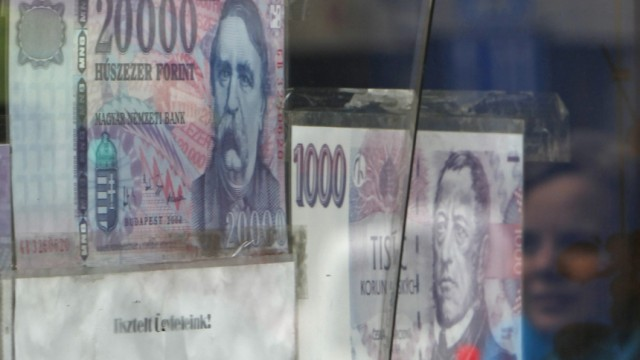 A woman walks past a money changer in Budapest