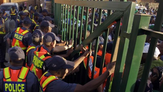 Südafrika: Verzweifelt versuchen Polizisten imMakhulong-Stadiondie aufgebrachten Fans zurückzuhalten.Fünf Tage vor Beginn der Fußball-WM brach dort eine Massenpanik aus.
