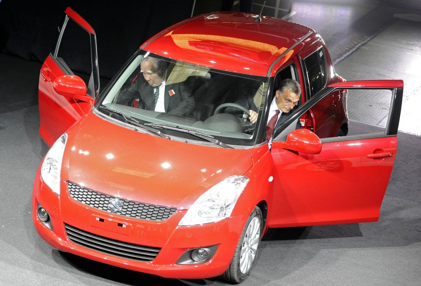 Suzuki Motor Corp CEO Osamu Suzuki and Hungary's PM Viktor Orban get out of a new Suzuki Swift during its unveiling at the company's factory in Esztergom