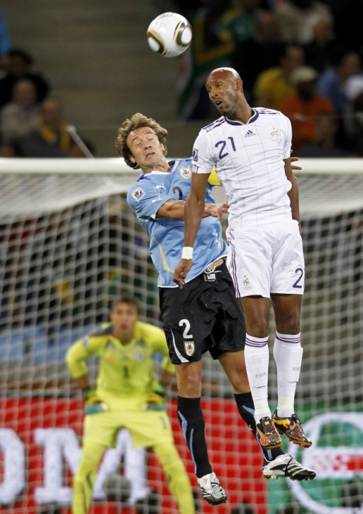 Uruguay's Lugano battles for the ball with France's Anelka during the 2010 World Cup Group A soccer match at the Green Point stadium in Capetown