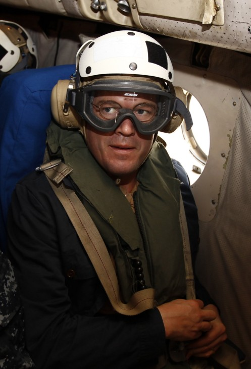 Guttenberg wears protective googles and a helmet after boarding a U.S. Navy aircraft at the airport of the Italian city of Sigonella