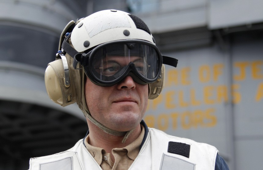 Guttenberg wears protective googles and a helmet on flight deck on board nuclear-powered aircraft carrier USS Harry S. Truman at an undisclosed position