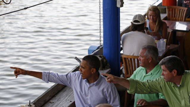 U.S. President Obama looks out over water with Alabama Governor Riley during visit to Tacky Jack's restaurant in Orange Beach, Alabama