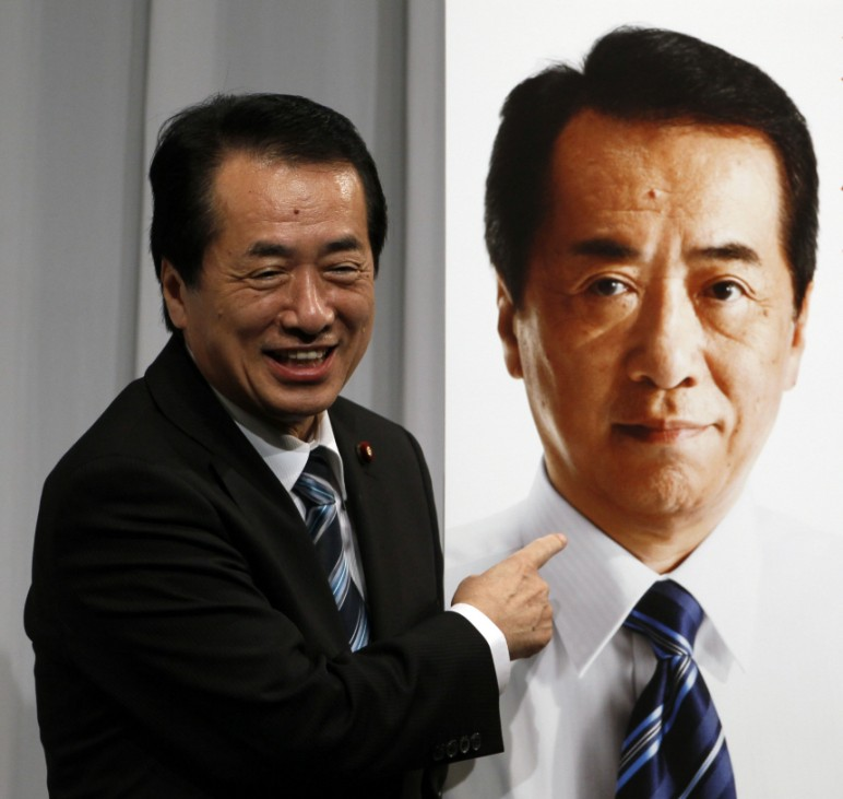 Japan's Prime Minister Naoto Kan points to a poster of himself during a news conference in Tokyo