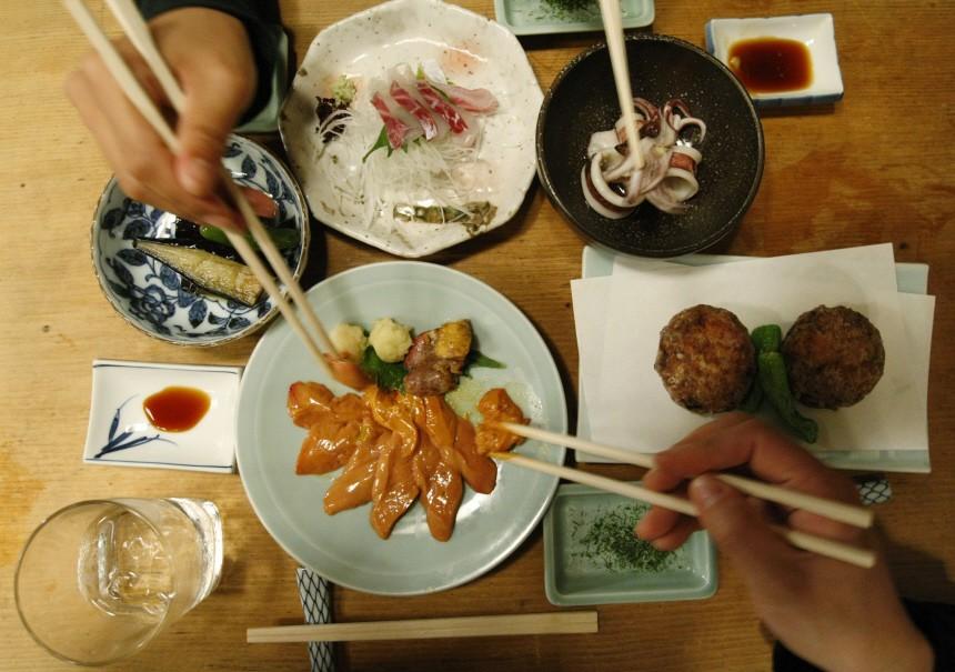 People share dishes at Japanese traditional 'Izakaya' pub named Saiki in Tokyo