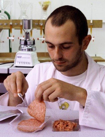 CHEMICAL ANALYST AT THE LOUIS PASTEUR INSTITUTE IN BRUSSELS TESTS A SAMPLE OF SALAMI