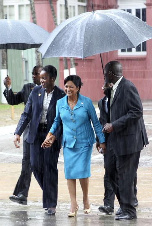 Trinidad and Tobago's Prime Minister Kamla Persad Bissessar walks in the rain in Port of Spain