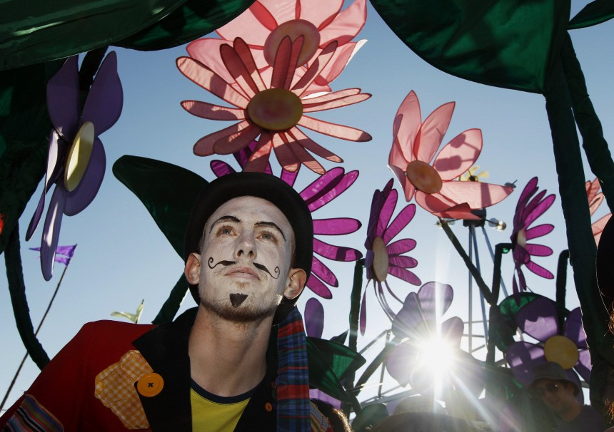 A festivalgoer in costiume sits under painted flowers at the Glastonbury Festival 2010 in south west England