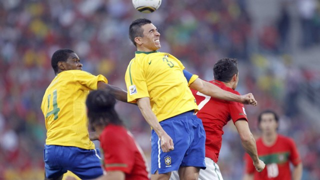 Brazil's Juan and teammate Lucio fight for the ball with Portugal's Cristiano Ronaldo at Moses Mabhida stadium in Durban