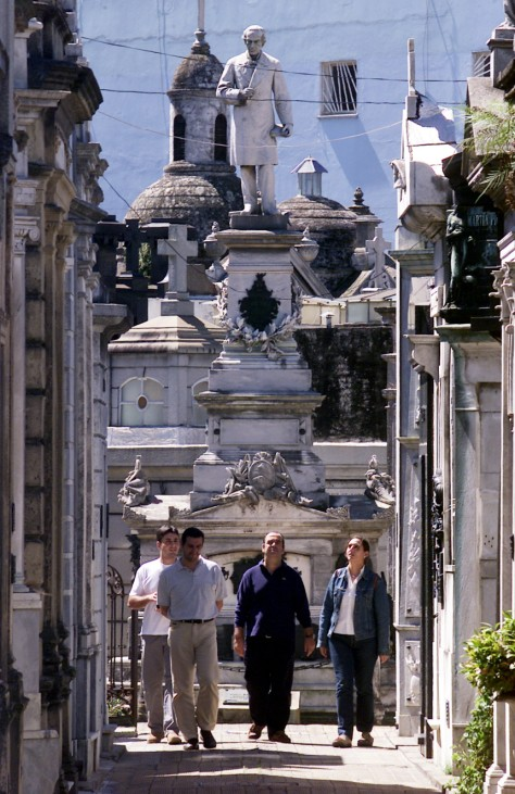 COUPLE WALK PAST MAUSOLEUMS IN BUENOS AIRES' RECOLETA CEMETERY