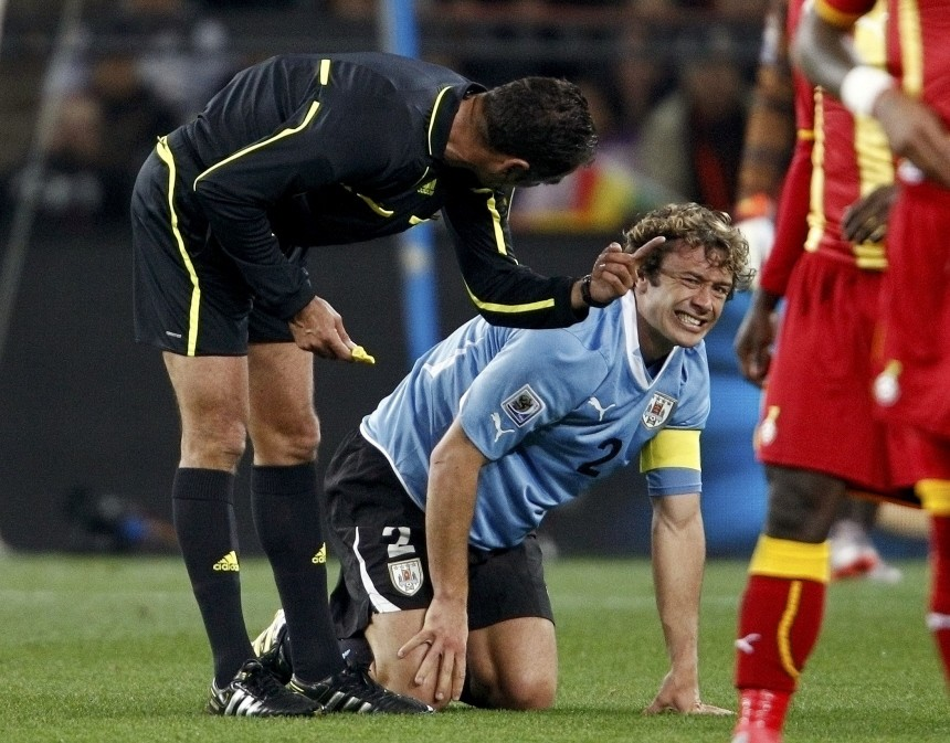 Referee Benquerenca has a word with Uruguay's Lugano during a 2010 World Cup quarter-final soccer match against Ghana at Soccer City stadium in Johannesburg