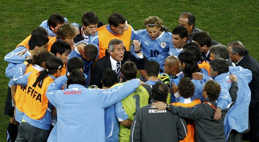 Uruguay's head coach Oscar Washington Tabarez talks to his team before the start of extra time at Soccer City stadium