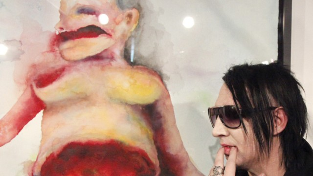 U.S. singer Manson poses in front of one of his paintings in Vienna