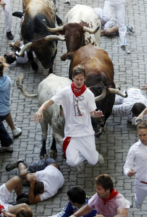 A runner runs in between the horns of a Penajara fighting bull before the first day of the running of the bulls during the San Fermin festival in Pamplona