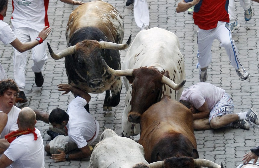 A fallen runner tries to push a Penajara fighting bull away during the first day of the running of the bulls during the San Fermin festival in Pamplona
