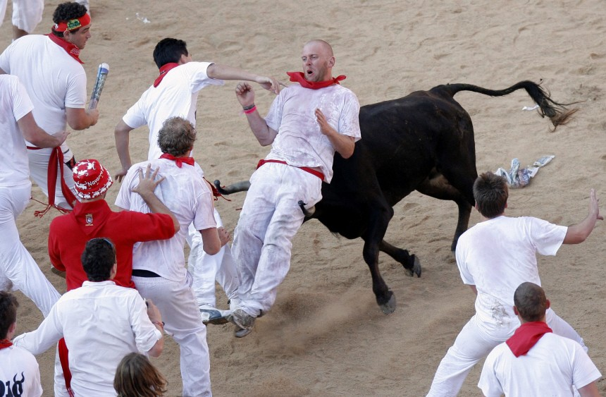A reveller is tossed by a fighting cow during festivities in the bull ring during the San Fermin festival in Pamplona