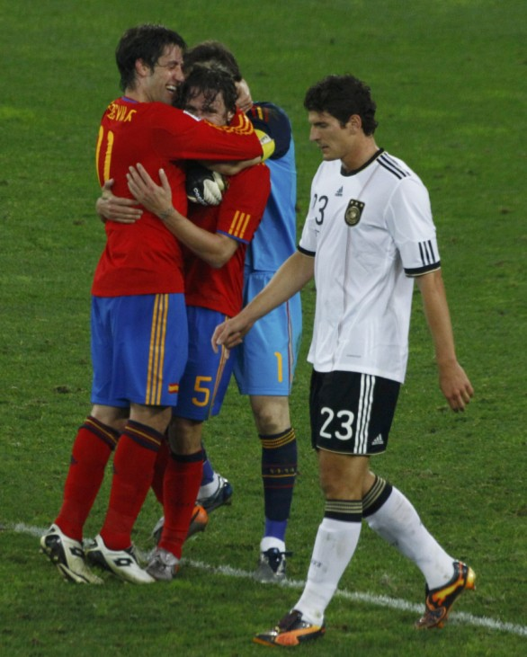 Spanish players celebrate their victory as Germany's Mario Gomez walks past after their 2010 World Cup semi-final soccer match at Moses Mabhida stadium in Durban