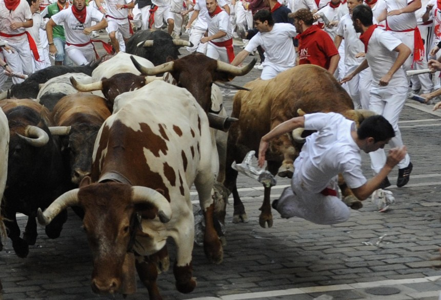 A runner is knocked down by a Cebada Gago fighting bull at Estafeta Corner during the second running of the bulls on the third day of the San Fermin festival in Pamplona.