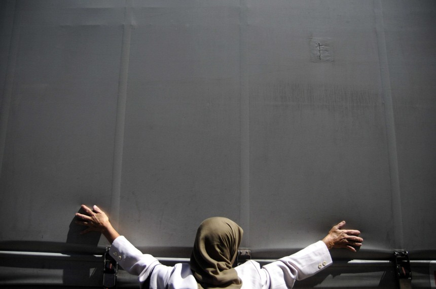 A Bosnian Muslim woman puts her hands on the bus in Sarajevo