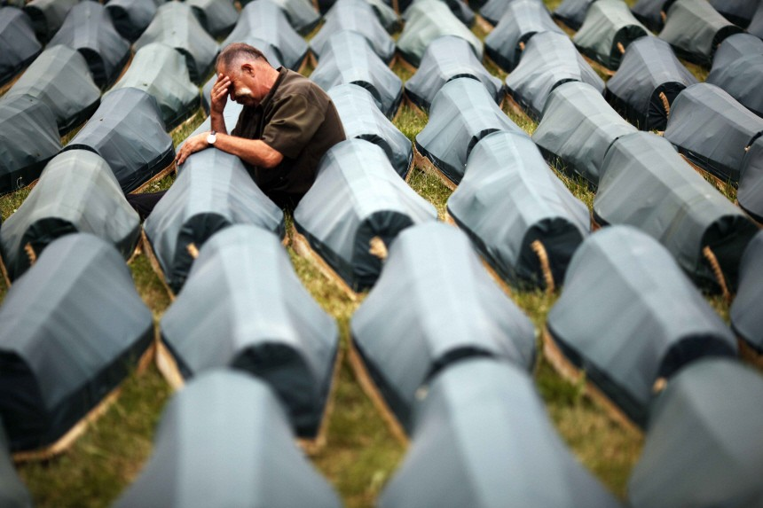 Muslim cries beside coffin of his son among 534 newly identified victims of the 1995 Srebrenica massacre lined up for a joint burial in Potocari