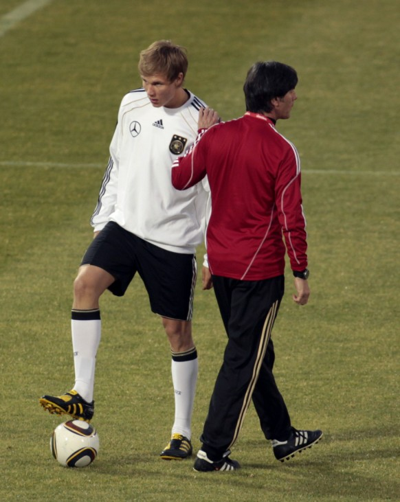 Germany's coach Loew walks past Badstuber during a training session in Pretoria