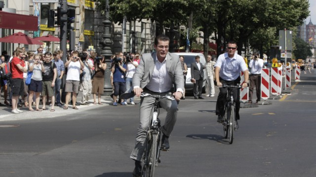 German Defence Minister zu Guttenberg leaves on bicycle after book presentation in Berlin