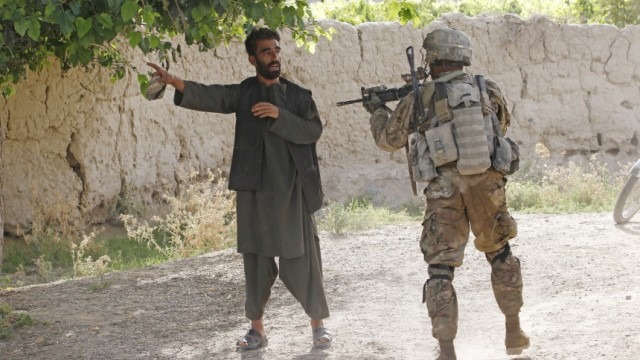 US soldier orders a man to lie on the ground during a patrol near the village of  Khersak