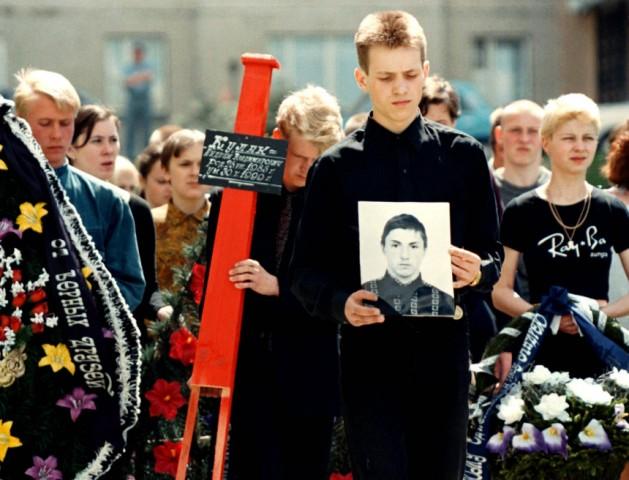 A Belorussian boy holds a portrait of his dead friend in Minsk